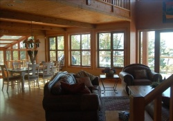 wood living room with leather chairs and many windows/doors, dining table in background, pet friendly by owner vacation rentals in vancouver