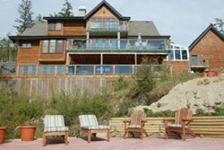 very large home, 3 or 4 stories with balcony/decks on each floor, view of the back of the house with lawn furniture and beach in the foreground, pet friendly by owner vacation rentals in vancouver