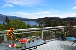 panoramic mountain views from a balcony with outdoor furniture and table set with sunflowers and appetizers, pet friendly by owner vacation rentals in vancouver